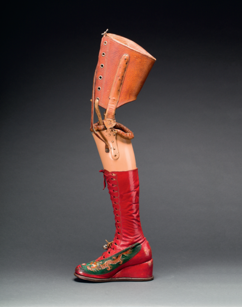 A picture of Frida Kahlo's prosthetic leg, photographed against a grey background. The prosthetic shows a leather part above the knee, where the prosthetic is attached to the amputated leg. The leather part is attached to a plastic, flesh-colored lower leg with two hinges, allowing the leg to bend. The lower leg is wearing a red lace-up boot with a wedge. On the side of the foot Kahlo painted an orange Chinese dragon on top of a green background. Two metallic bells are hanging from a salmon-colored ribbon, attached to the shoelaces at the height of the ankle.